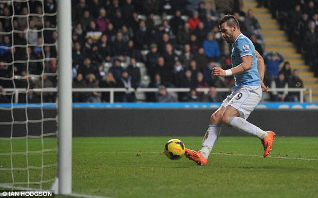 Easy does it: Negredo slides the ball into an empty net to seal a 2-0 win for title-chasers City