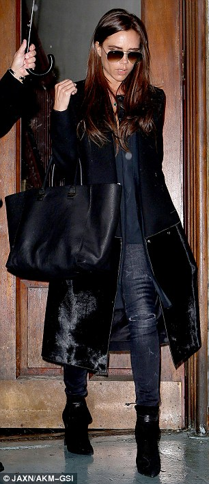 Walk this way: Posh was stylish as ever in dark blue ripped jeans, a matching navy blouse, long black coat with black fur detail and short black suede boots with leather ankle ties, teamed with an oversize black leather bag