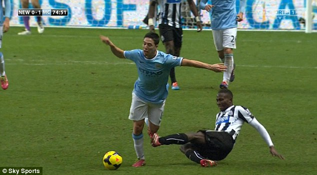 More than a nibble: The Newcastle man had two swipes at Nasri's knee as he tried to stop him