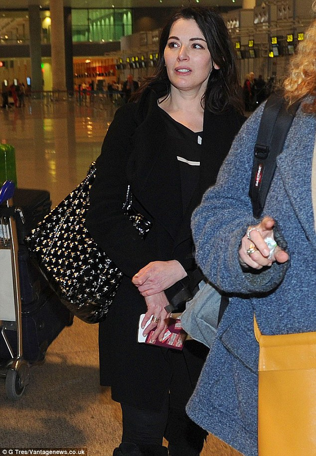 Looking good: Nigella, as ever, looked elegant in an all-black ensemble for her journey home