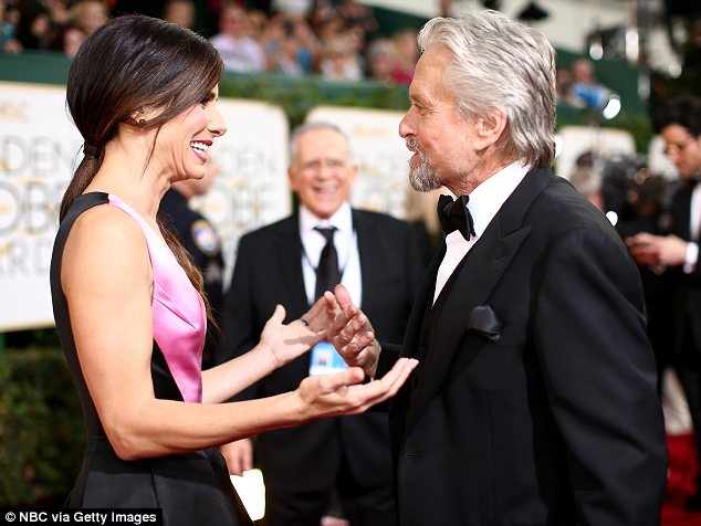 Catching up: Michael chatted with Sandra Bullock at the Golden Globes as he arrived solo