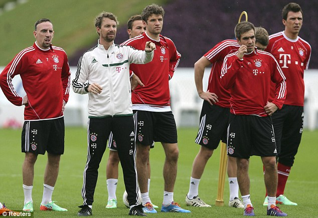 Training day: Franck Ribery (left), Thomas Muller (3L) and Phillip Lahm (2L) take instructions before the resumption of the Bundesliga