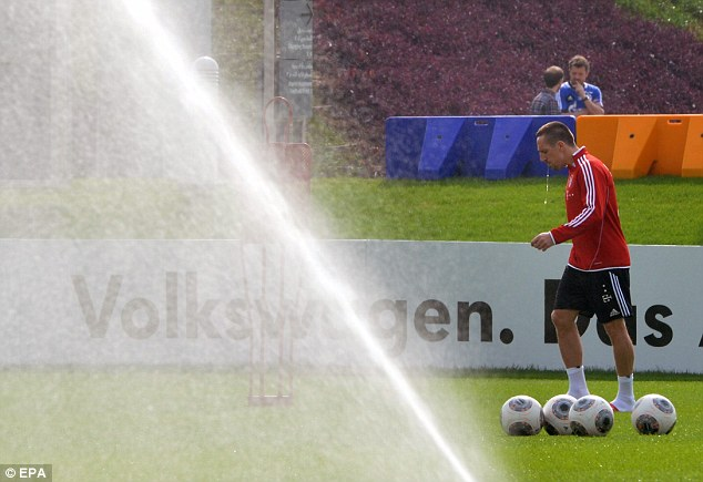 Spray it again: Franck Ribery avoids the sprinklers at the hotel's training facilities