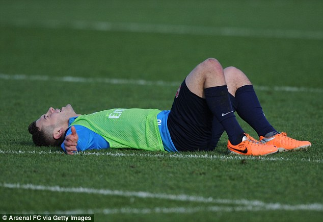 Out of steam: Jack Wilshere lays on the ground exhausted during Arsenal's training session at London Colney