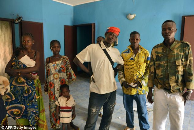 Anti-Balaka Christian militiamen pose with members of their families as they stay indoors in a home in Boy-Rabe district in Bangui