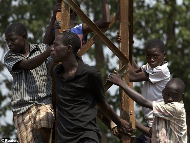 People climb a metal post as they listen to a speech give by the Central African transitional parliament chief  Alexandre-Ferdinand Nguendet
