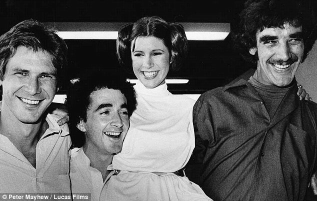 Rare smiles: Peter Mayhew, who played Chewbacca in the first Star Wars trilogy, is seen here with Harrison Ford (left) and Carrie Fisher (center) in never seen before shots shared by the actor in early January
