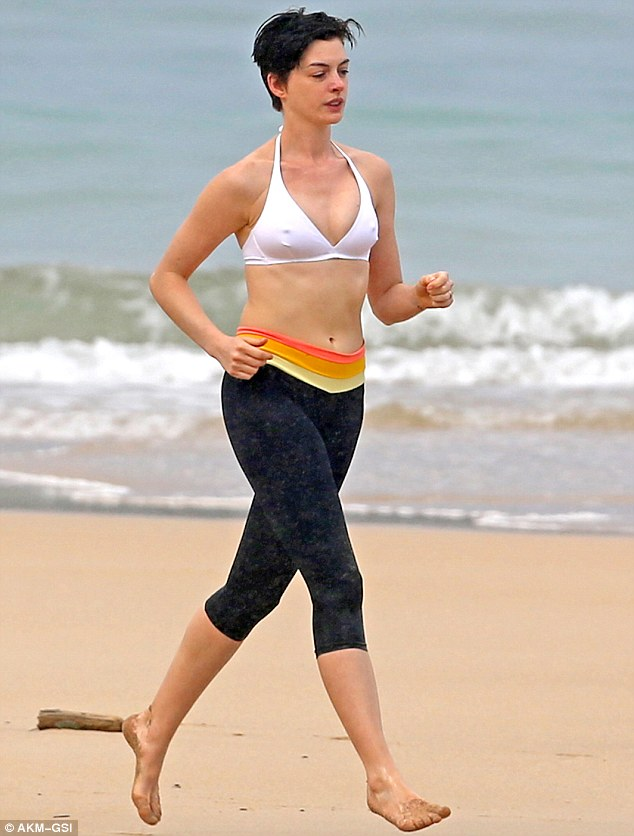 No rest for the wicked! The 31-year-old may have been on holiday but that didn't affect her exercise routine, donning black three-quarter leggings with a fun red, orange and yellow striped waistband and a white bikini top for her beach jog