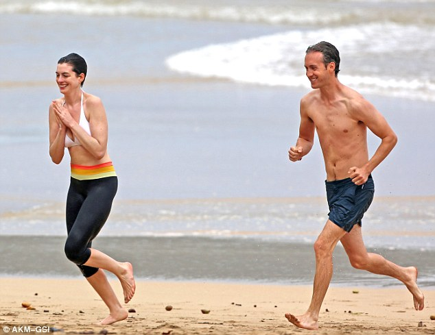 The couple that runs together... Husband Adam Shulman also got in on the act, joining his wife for a jog followed by a dip in the cool ocean
