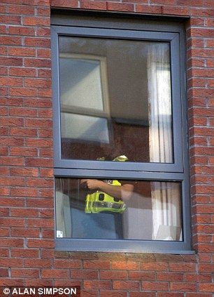 An officer speaks to someone in a window, believed to be the home of the missing boy