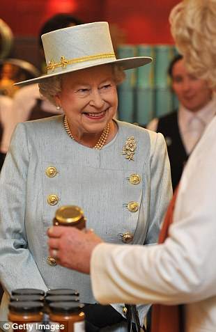 Queen Elizabeth is shown jars of preserves while visiting Fortnum & Mason store