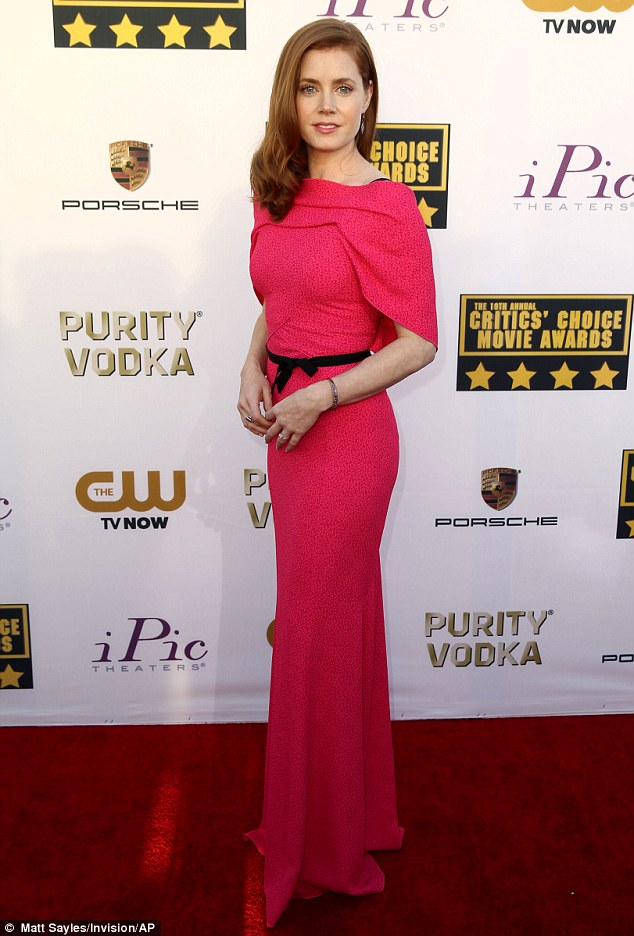 Award-winning fashion: The 39-year-old oozed Old Hollywood glamour in her form-fitting dress that featured draped shoulder detail and a thin black bow belt that cinched in her already tiny waist