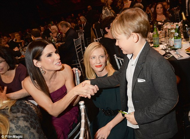 Getting to know you! Cate looked on proudly as Sandra shook hands with her adorable sun Ignatius Martin Upton during the ceremony
