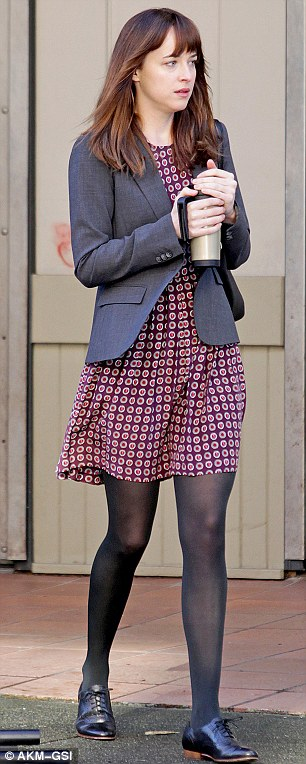 Off to work: Dakota wore a pretty patterned dress with tights and brogues for a different scene earlier on