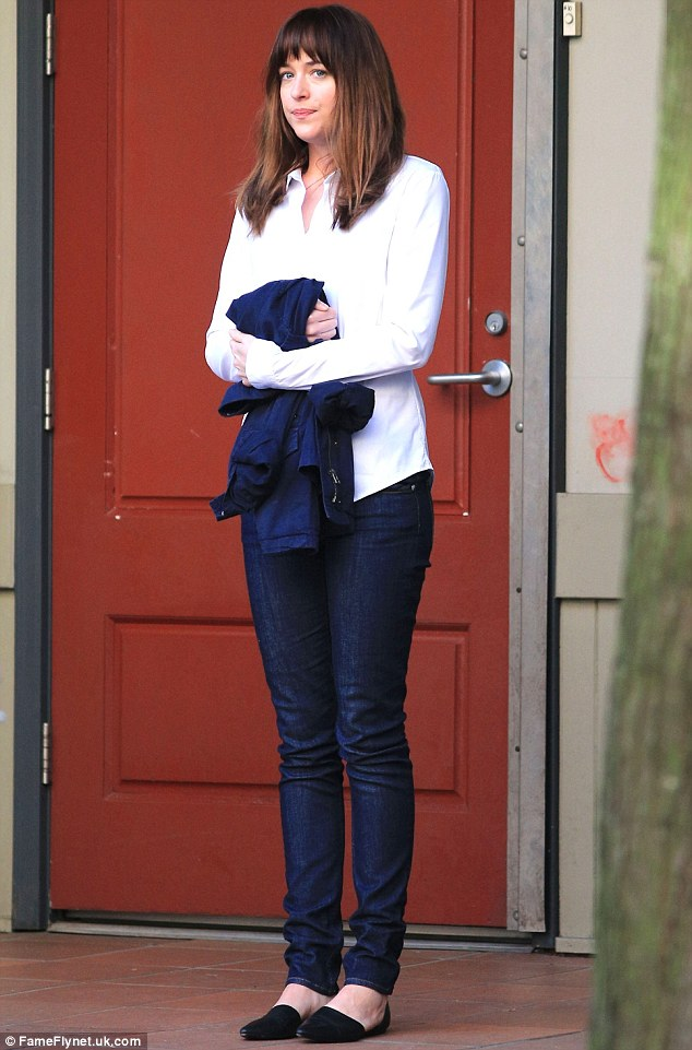 Pre-drenching: Dakota was seen in a pair of dark, skinny jeans and a crisp white shirt