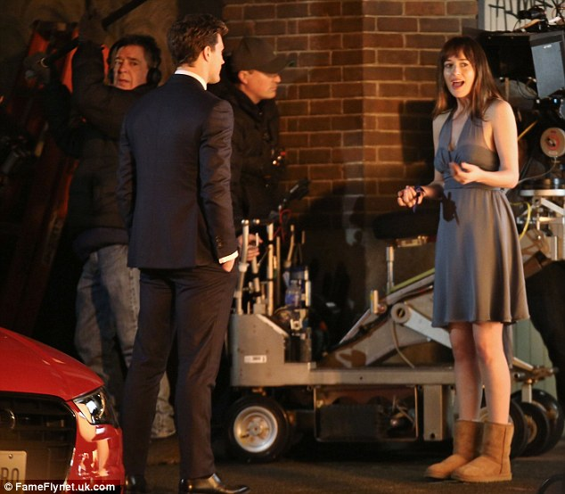 Comfort over style: Dakota opted for beige UGG boots which looked odd teamed with her smart dress