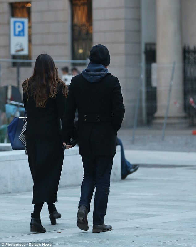 Holding hands: The pair were dressed fairly alike as they wrapped up warm against the cold weather