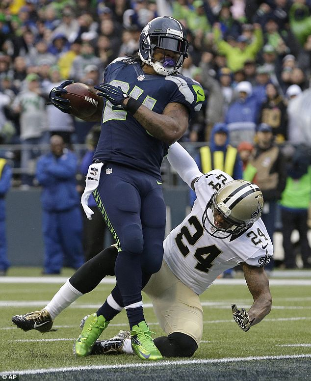 Two games away: Seahawks running back Marshawn Lynch, top, scores past New Orleans Saints in the NFC divisional playoff game. Seattle face San Francisco in the NFC Championship on Sunday