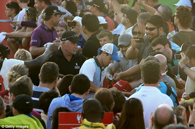 Centre of attention: McIlroy signing autographs for local fans after the second round