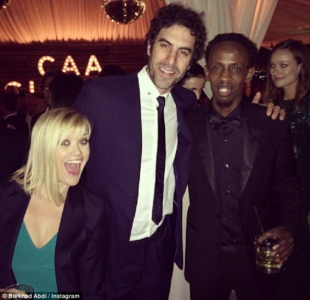 The A-list: Barkhad Abdi shows off pictures of his new friends Reese Witherspoon and Sacha Baron Cohen while enjoying the Golden Globes in Hollywood