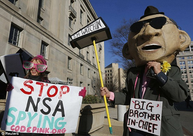 A protester in a mask depicting U.S. President Barack Obama calls for the U.S. eavesdropping on the leaders of close friends and allies to be stopped