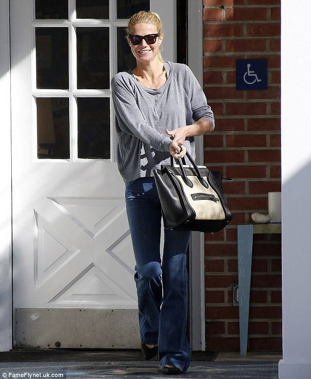 Movie star touch: Gwyneth carried a black-and-beige designer handbag as she left a building