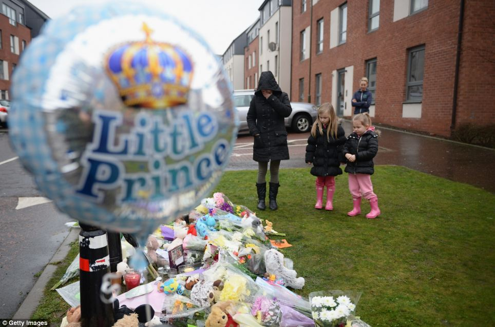 A woman and two children pause emotionally at the site of the tributes. In the foreground, a balloon tribute reading 'Little Prince'