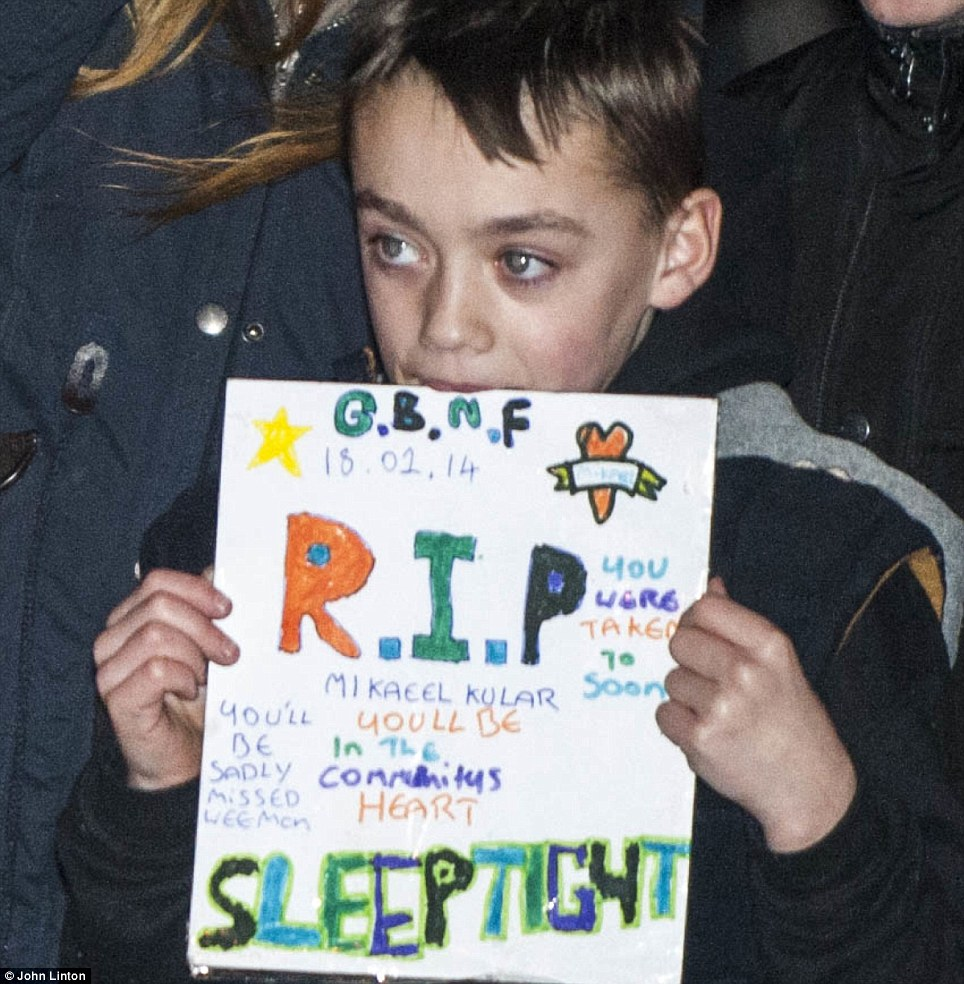 RIP: A boy holds up a placard saying 'Mikaeel Kular, you'll be missed in the community's heart, sleeptight'