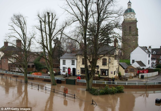 At risk: The river Severn threatens the recently-built flood defence system in Upton-upon-Severn, England