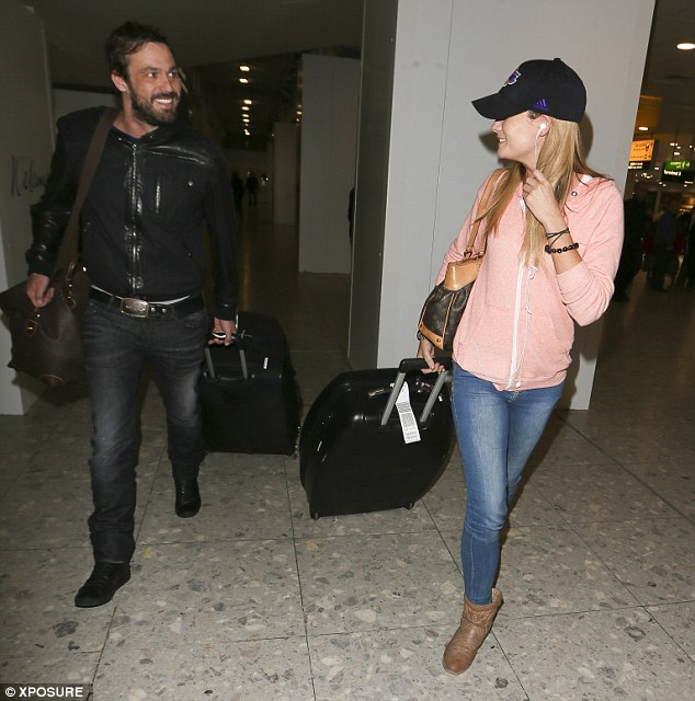 He's pleased: Jamie Lomas sports a broad grin as he makes his way across Heathrow Airport with Chloe Peers on Sunday