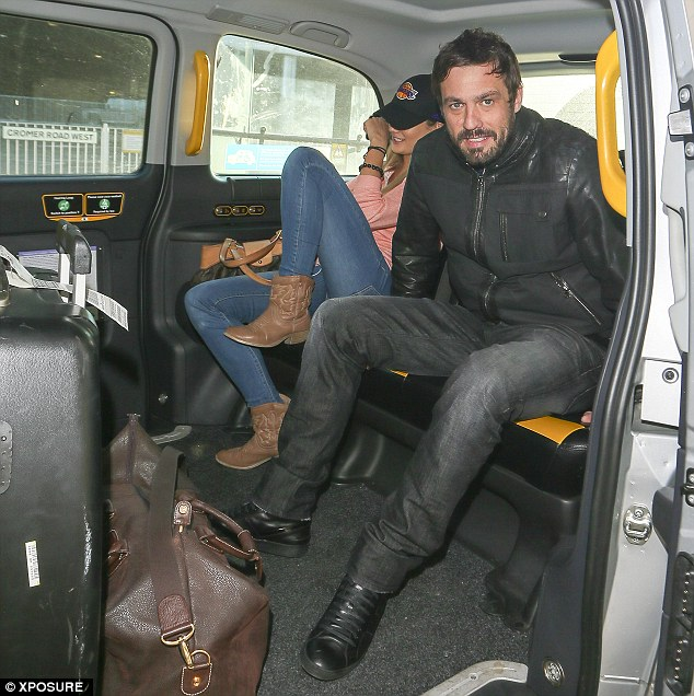 Don't mind us: Jamie and Chloe settle in the rear of a people carrier after making an exit from Heathrow