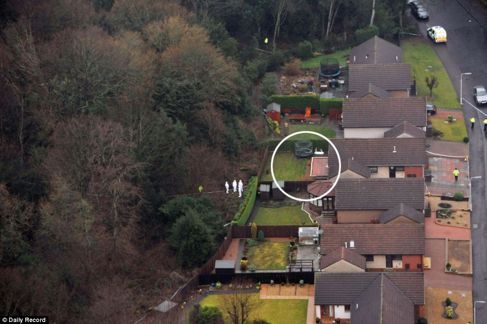 Find: Forensic experts in white overalls search the woods behind the back garden of the property (circled)
