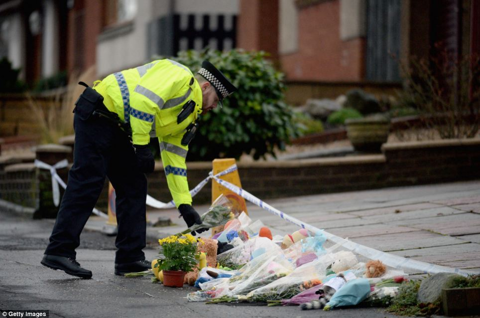 Support: A police officer lays flowers outside the bungalow in Kirkcaldy