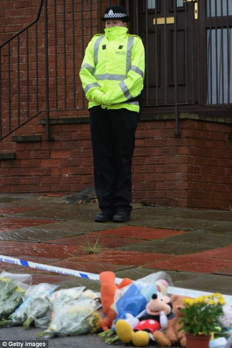 Guard: A woman police officer stands guard outside the home