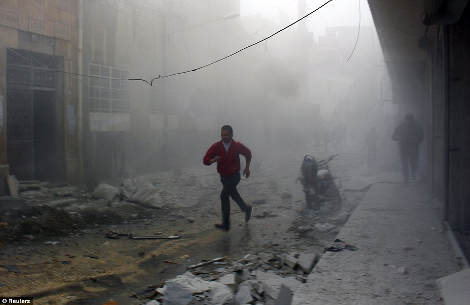 Running to safety: Residents run away from collapsing buildings after an alleged air strike by forces loyal to Syria's president Bashar Al-Assad in the Al-Maysar neighborhood of Aleppo
