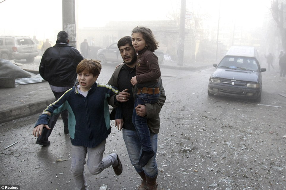A resident holds on to a child who survived shelling in the air attack as they flee the area
