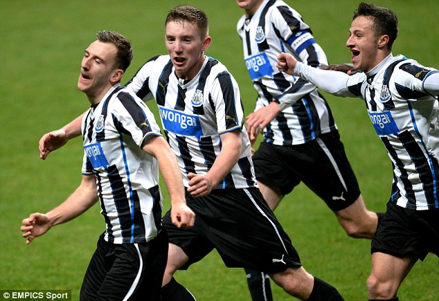Man of the moment: Newcastle's Number 9 Quinn is mobbed by teammates after scoring