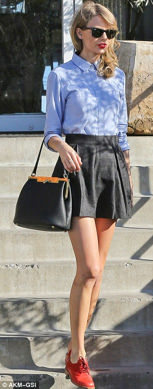 School girl: The 24-year old singer songwriter donned a black pleated skirt pulled up high on her waist, a blue button down shirt, and red oxfords