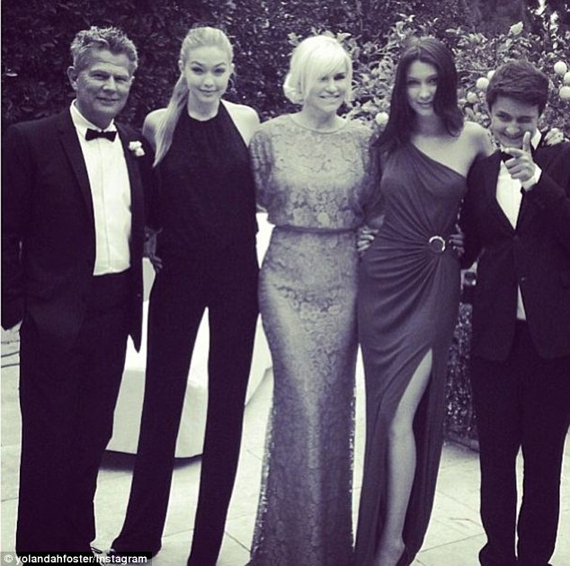 Modern day: Mrs Foster looks remarkably the same in a recent photo with her three children and husband, David Foster