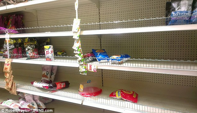Bare shelves: Crowds of shoppers cleared the shelves in the 99p Store in Wrexham when it halved its prices