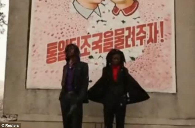 Monumental: Pacman and Peso stand in front of a Korean advertisement board on a Pyongyang square