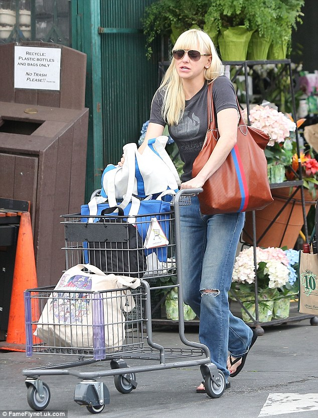 Carted off: The 37-year-old was casually dressed in ripped jeans and flip-flops for her shopping errand