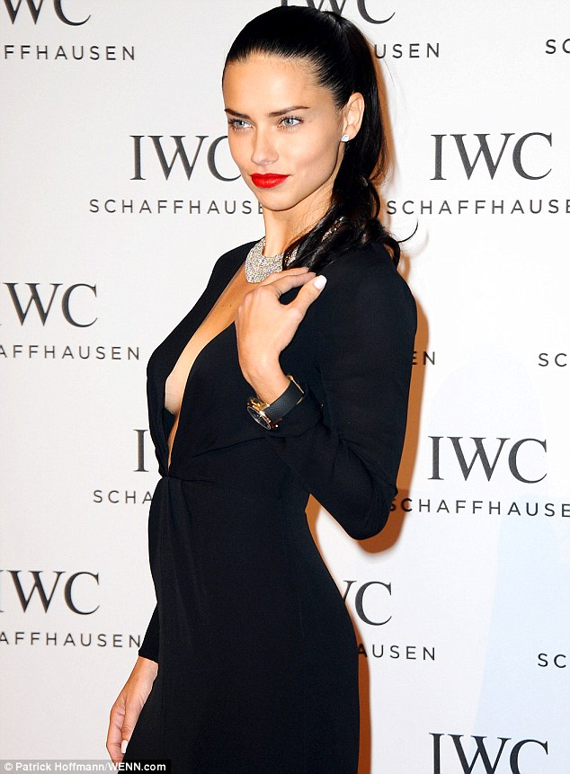 Dare to bare: Wearing her long raven locks slicked back from her face, the 32-year-old model injected a bold pop of colour to her look with a slick of pillar-box red lipstick, while adoring her decolletage with a stunning, glittering diamond necklace