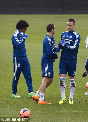 Serious: Terry has eyes only for his fellow defender while Willian tried to keep warm in the background