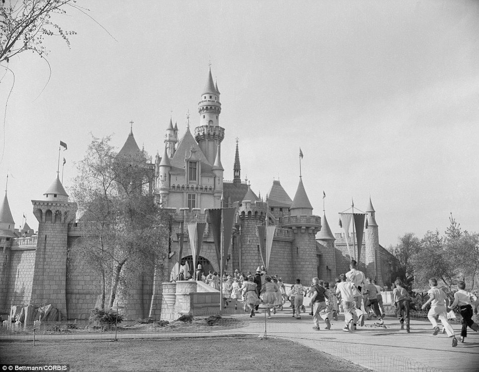 First guests: Hollywood celebrities and their children race off to explore Sleeping Beauty's castle on the opening day of the original Disneyland in Anaheim,  California in July 1955
