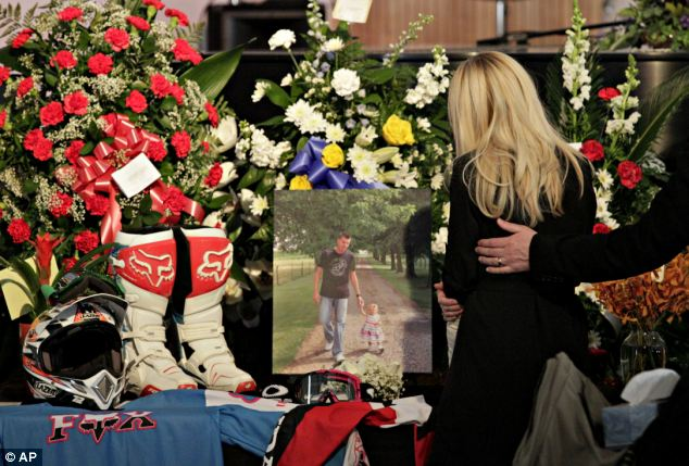 Loss: Mrs Oulson looks at a photo of her husband Chad and their daughter Alexis, along with her husband's helmets and motocross gear, on display during a memorial service on January 18