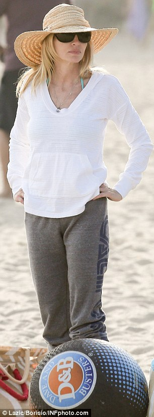 All smiles: Camille looked happy as she later strolled along the beach in casual clothes and flip flops