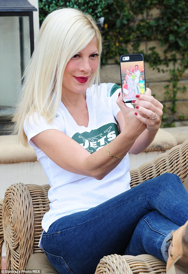 What divorce? Tori Spelling apparently hoped to quash rumours of a pending divorce from husband Dean McDermott as she posed for an 'impromptu' selfie in LA on Tuesday, during which she flashed her wedding ring and her phone case featuring a sweet family portrait