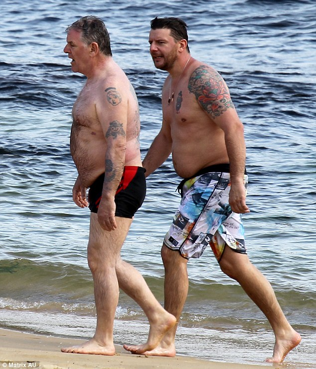 Like father, like son: Manu and his father, also a chef, were seen strolling up the sand from the shore
