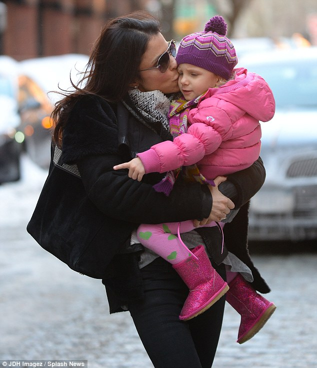 Snow bunny: Bethenny Frankel snuggled up with her daughter Bryn but the little girl seemed far more interested in the snow than kisses in New York on Wednesday